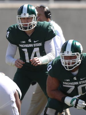 Michigan State quarterback Brian Lewerke runs the offense while guard Tyler Higby looks on during the spring game at Spartan Stadium, Saturday, April 1, 2017.