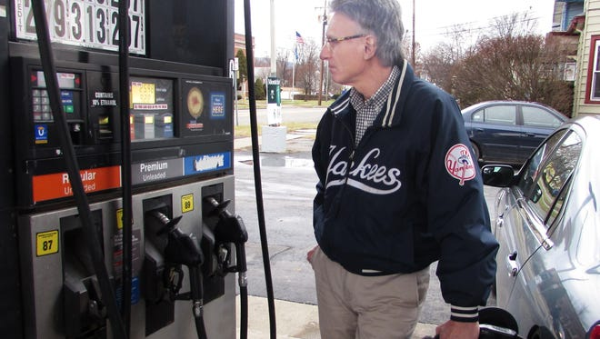 Frank Messina, of Elmira, fills up his Lincoln on Sunday at the Mobil station on the corner of Church and Hoffman streets in Elmira. Gas prices should continue to drop through the New Year's holiday, according to AAA.