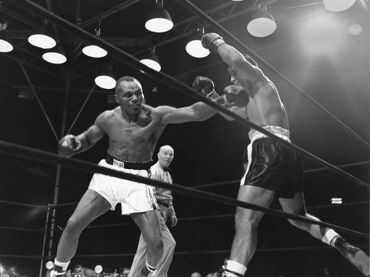 In this file photograph taken Sept. 23, 1952, in Philadelphia, Jersey Joe Walcott, left, swings at Rocky Marciano during a fight won by Marciano.