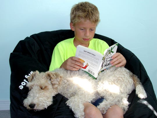 Conner Turner reads a book while TheraPaw dog Score