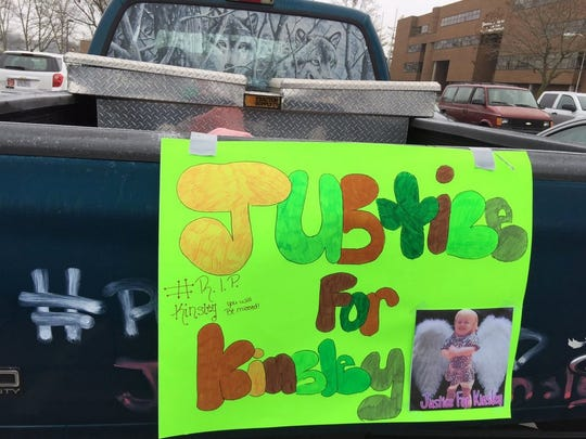 A handmade sign on a truck in the parking lot of the Middletown Municipal Court during one of the first hearings after 2-year-old Kinsley Kinner was killed.