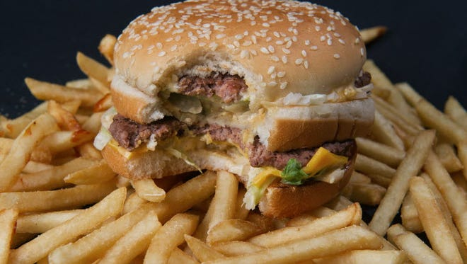 A partially eaten McDonalds' Big Mac hamburger atop French fries in 2010.