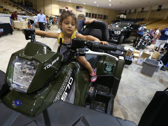 2-year-old Amaryllis Beck of Morristown gets the feel for a Park Police ATV during Morris County Park Police and the Morris County Park Commission sponsored 'National Night Out,' an evening of awareness and fun with free food, free entertainment, free skating, giveaways and free attractions. August 2, 2016, Morris Twp, NJ