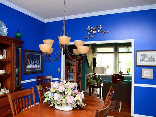 """The dining room of the Barb and Ernie Harwig's home is currently painted a bright blue. Barb Harwig is not afraid of color and likes to change the paint colors in the house often. She said her friends joke that they never know what color the house is going to be when they step inside. """"They say 'we figured you can live on the top of the mountain cause you're insulating with paint,'"""" she joked."""