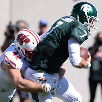 Senior quarterback Tyler O'Connor is sacked by Wisconsin