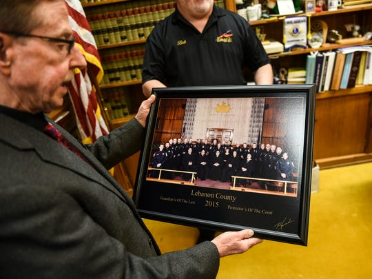 Sheriff Bruce Klingler, looks at the photo after local photographer Robert Howard made of all five Lebanon County judges and all 21 sheriff deputies on Friday, March 4, 2016. This is the first time a picture like this has been taken. The photo was taken on Oct. 19, 2015 and Howard donated his services and the print which hangs in the judge's chambers.
