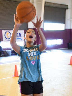 """Gabriella Mata gives a battle cry for Narnia, helping her shot go in, at the Bank of Guam Youth Basketball Camp in the Tamuning Gym on Dec. 23, 2016. The battle cry was """"To bring honor to my clan,"""" said Mata."""