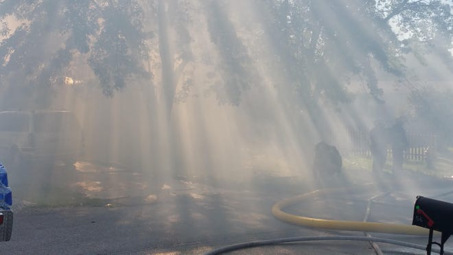 Intense smoke from a house fire in the 20 block of Straw Hat Drive obscures the view of the fire, picking up the rays of sunlight coming through the trees. One person was seriously injured in the fire, according to Melinda Salas, who lives here.