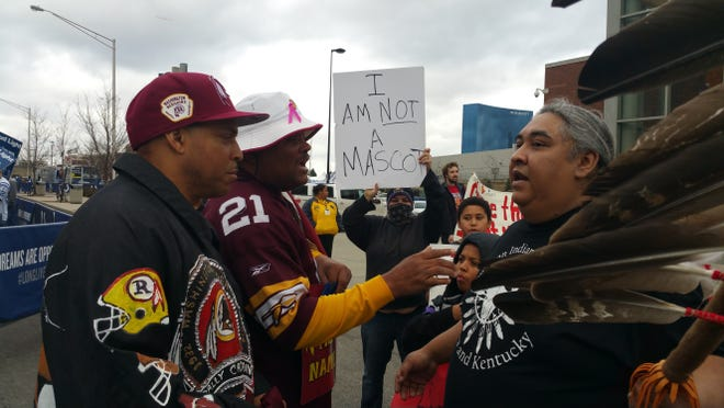 Washington Redskins fans Stephen Boyd, far left, and Rodney Johnson exchange words with Albert Running Wolf, president of the American Indian Movement of Indiana and Kentucky, in front of Lucas Oil Stadium before the Indianapolis Colts took on the Washingotn Redskins.