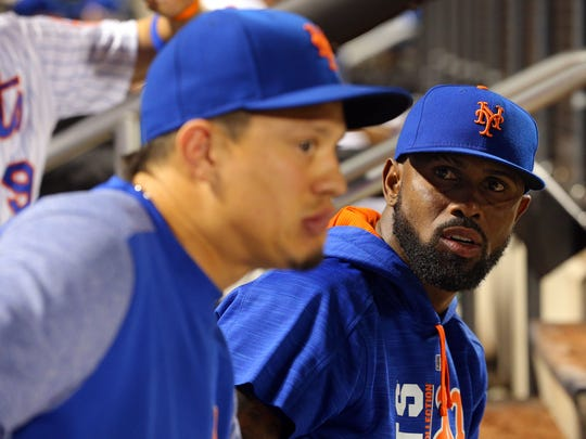 Mets shortstop Jose Reyes (7) talks to New York Mets third baseman Wilmer Flores (4) during the ninth inning of a game against the New York Yankees at Citi Field on Wednesday. Both players were unavailable for the game because of injuries.