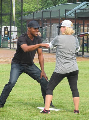 Barry Larkin helps one of the Dukes with her batting skills.