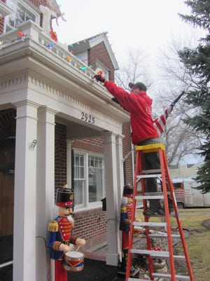 Andrew Pfeifle of Christmas Decor changes a Christmas light bulb at the house of one of the company's 130 Great Falls customers.