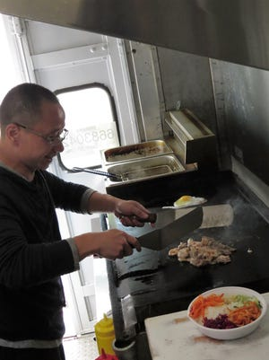 Chef Bruce Li cooks meat to top a combination Korean stone bowl rice dish on the hibachi-style flat top in his new food truck. He also offers hibachi meat and vegetables, spring rolls and his version of bang bang shrimp.