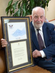 Volunteer Milford O'Brien shows off his award from the president as one of the nation's top volunteers.