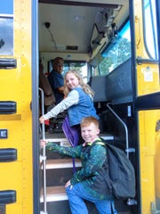 Delaney Pickens, 7, in second grade and D'Arby Shaughnessy, 8, in fourth grade, board the school bus as they begin the new school year..
