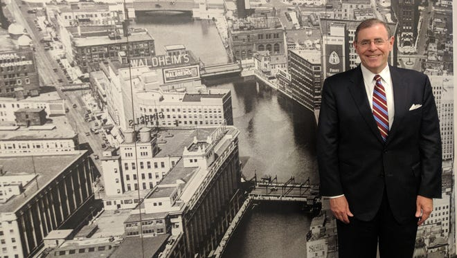 James T. Barry III stands in front of a wall mural made from an aerial photo of downtown Milwaukee taken in 1929.