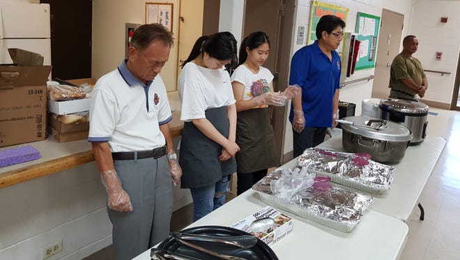 Guam Gadao Lions Club says a prayer on June 30 before serving food to more than 100 homeless individuals at the Dededo Mayor's Office. Gadao Lions Club has been providing food monthly in Dededo and Hagatna for 17 years. The club strives to provide more benefits and funding to go towards services. Pictured from left: Gary Kim, Stella Bae, Tori Chung and Inwhan Han.