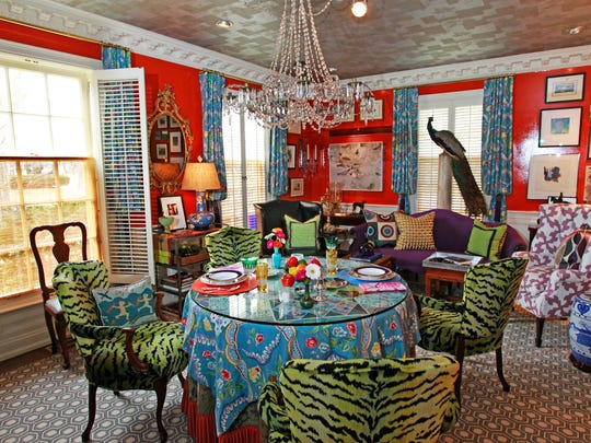 The dining room provides traditional sitting as well as unconventional areas for guests to dine and lounge. The walls were painted Charlottes Locks, which is a vibrant orange color in a high gloss. The table is covered with a piece of glass and with family and found china. There are also old cruise ship menus on the table.