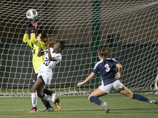 Estero goalkeeper Teaghan McArdle (24) makes a save in front of Montverde Academy's Jody Brown (20) as Estero's India Fortner (3) watches during the first half of an Class 4A FHSAA State Soccer Championship game Friday, Feb. 23, 2018, in DeLand, Fla. (Phelan M. Ebenhack for the News-Press)