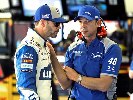 Jimmie Johnson, left, talks with crew chief Chad Knaus in the garage during a practice session for the NASCAR Sprint Unlimited auto race at Daytona International Speedway, Friday, Feb. 12, 2016, in Daytona Beach, Fla. (AP Photo/Terry Renna)
