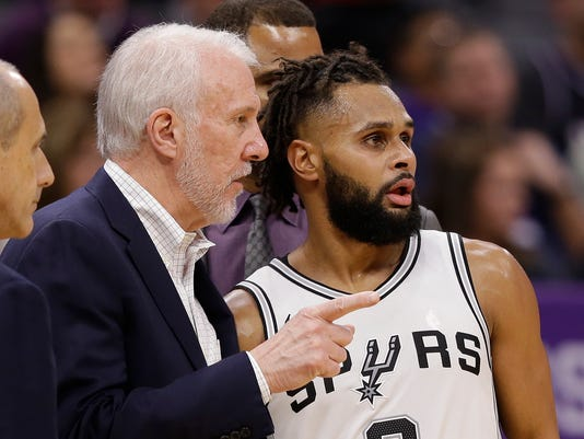 San Antonio Spurs head coach Gregg Popovich, left, talks with guard Patty Mills during the second half of an NBA basketball game against the Sacramento Kings, Monday, Jan. 8, 2018, in Sacramento, Calif. The Spurs won 107-100. (AP Photo/Rich Pedroncelli)