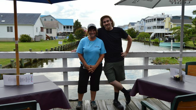 Linda Guckin, owner of Fin Alley in Fenwick, smiles with executive chef, Alex Ljuba.