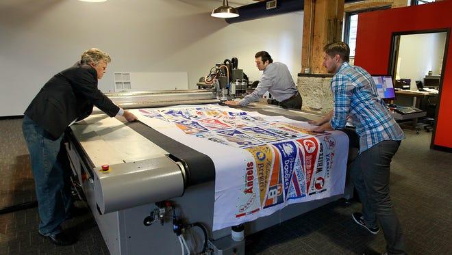 Steen Mikkelsen, Nikolai Mikkelsen and Sean Lawrence set up their new digital die cutting machine. August 15, 2013.