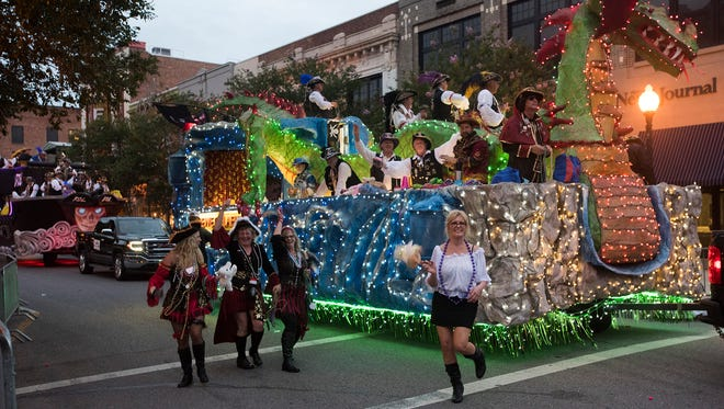 The Fiesta of Five Flags parade rolls through the streets of downtown Pensacola Friday night to the delight of area residents.