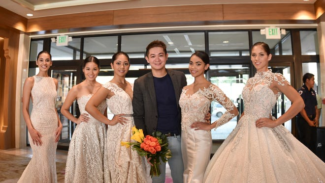 Designer Michael Leyva takes a picture with the Guam Manila Bridal and Honeymoon Showcase bridal show models at Guam Reef and Olive Spa Resort in Tumon on Oct. 24.