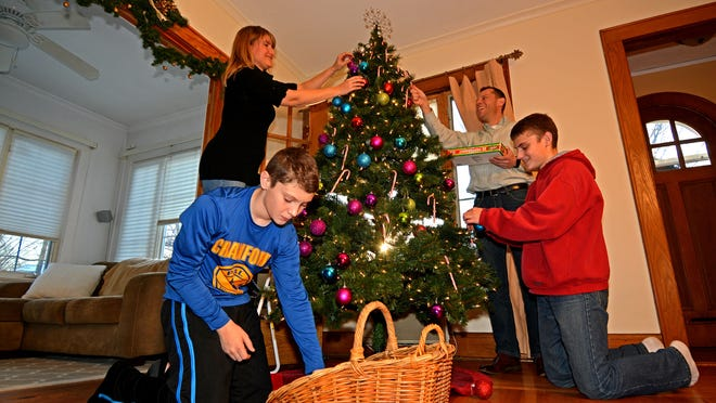 Judy Reggio, 46; her ex-husband, John Reggio, 44; and their two kids, John, 14, and C.J., 12, decorate the family Christmas tree. The couple's divorce was final in February, though they've been separated since 2010.  Some divorced people try to have better relationships with their exes and gather for the holidays.