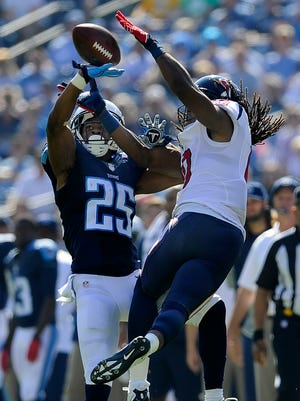 Titans cornerback Blidi Wreh-Wilson (25) breaks up a pass intended for Texans wide receiver DeAndre Hopkins (10) during the first quarter at LP Field Sunday Oct. 26, 2014, in Nashville, Tenn.