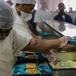 Prisoners supervised by Aramark serve food at a prison near Jackson.