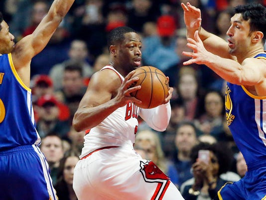 FILE - In this March 2, 2017, file photo, Chicago Bulls guard Dwyane Wade, center, looks to pass between Golden State Warriors guard Patrick McCaw, left, and center Zaza Pachulia during the first half of an NBA basketball game in Chicago. (AP Photo/Nam Y. Huh, File)