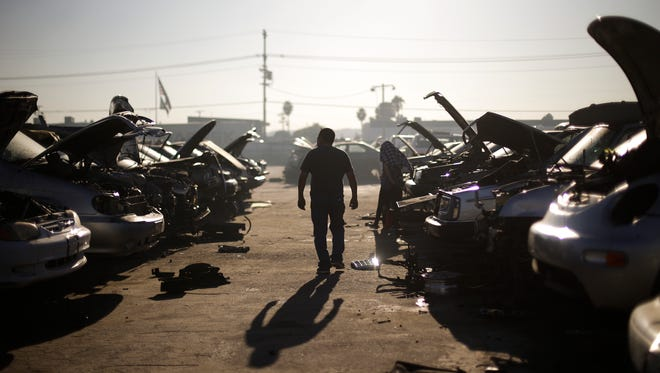 In this Wednesday, Nov. 11, 2015 photo, a man walks between junk cars at Aadlen Brothers Auto Wrecking, also known as U Pick Parts, in the Sun Valley section of Los Angeles. It's not just a junkyard or even a really big junkyard, but a living, breathing monument to Los Angeles pop culture. But the family business is closing on New Year's Eve, and everything must go by then, the cars, the shark, the arches, even the giant car-crushing machine. (AP Photo/Jae C. Hong)