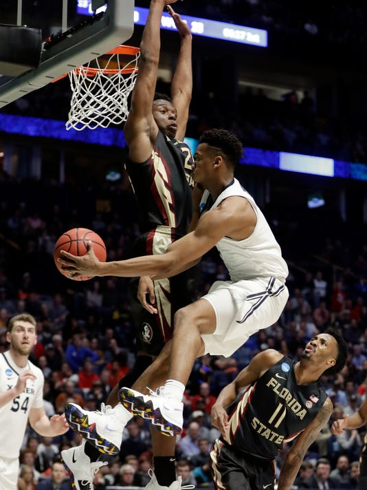Florida State forward Mfiondu Kabengele (25) blocks a shot to the basket by Xavier guard Paul Scruggs (1), during the second half of a second-round game in the NCAA college basketball tournament in Nashville, Tenn., Sunday, March 18, 2018. To the right is Florida State guard Braian Angola (11) and Xavier forward Sean O'Mara (54) to the left. (AP Photo/Mark Humphrey)