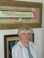 Pat Hopper, manager of the California Artichoke Advisory Board, stands in the board headquarters, the La Scuola building, formerly Castroville's old schoolhouse. Behind her is the artichoke queen sash from 1948, worn by Marilyn Monroe.