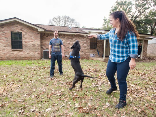 Austin and Michelle Lewis play with their dog Bane