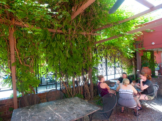 Patrons eat under a grape arbor in the outdoor dining