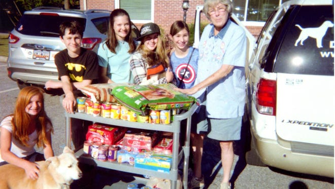 Shown are Central Presbyterian Youth Group who donated canned dog and cat food to Buster's Buddies Animal Rescue and Sanctuary, along with some of the dogs waiting for adoption. Shown, at right, is Elizabeth Fant, CEO of Buster's Buddies.