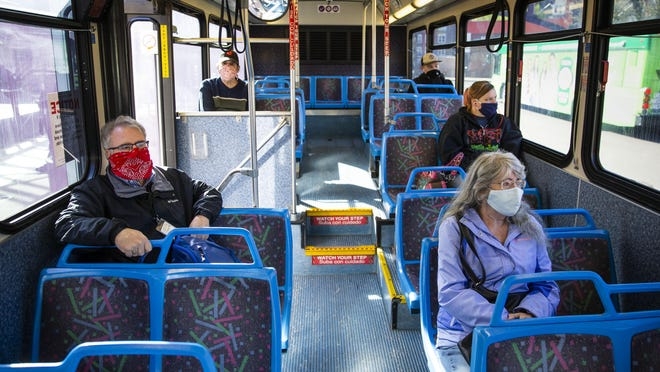 Passengers wear masks as ride an Lane Transit Department bus from downtown Eugene to the River Road area on the first day that masks were required for anyone on an LTD bus.