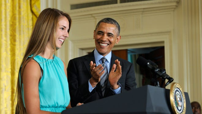 President Obama applauds Victoria Bellucci, a 2014 graduate of Huntingtown High School in Huntingtown, Md., as she introduces Obama to speak at the White House Healthy Kids & Safe Sports Concussion Summit on Thursday in the East Room of the White House in Washington. Bellucci played four years of women's varsity soccer where she was a team captain and an All-State selection. By the time her high school and club soccer careers ended in 2013, Bellucci had suffered five concussions.