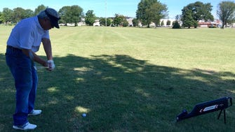 Retired physician Dr. Noel Florendo hits balls at the golf practice field on the east edge of Audubon Park.