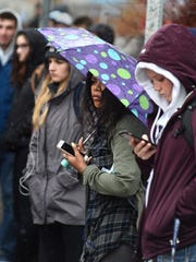 UNR students wait in the rain at a bus stop on Virginia Street on Thursday morning Nov. 16, 2017.