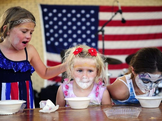 After winning the competition Caitlyn Masters, 7, left, cheers on her little sister, Maddy, 5, both of Bonita Springs in the ice cream eating competition Friday, July 4, 2014 at Riverside Park in Bonita Springs. Thousands came to celebrate the nation's independence with the annual Star Spangled Bonita event. It kicked off with a morning parade followed by celebration in the park featuring live music, food, games, annual bed races, eating contests, fireworks and more. (Corey Perrine/Staff)