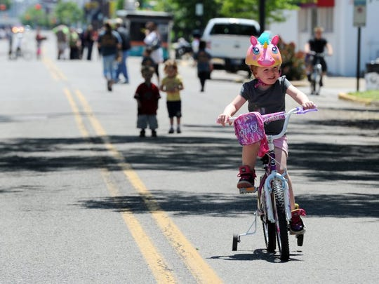 ERIN McCRACKEN / COURIER & PRESS Brooklynn Mitchell, 4, rides her bicycle on North Main Street during a past 'Evansville Streets Alive!' Festival.' I am glad they (the city) is doing this type,' her grandmother, Jolene Ling said.