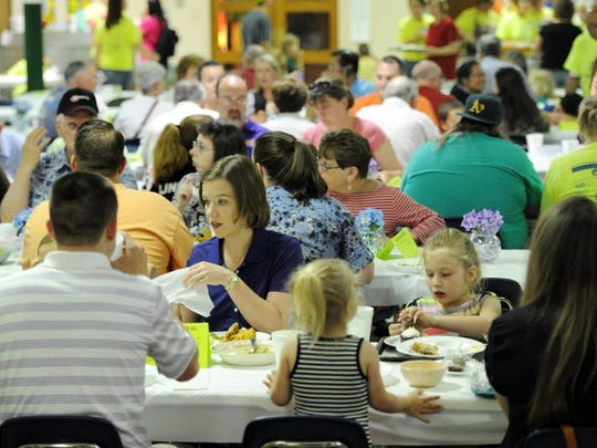 Catholic churches are known for hosting large food gatherings. During lent, it's fish fries on Friday. The photo shows families enjoying a dinner of Fried Chicken and the fixings at the Holy Rosary Catholic Church Summer Social on Thursday, May 14, 2015.