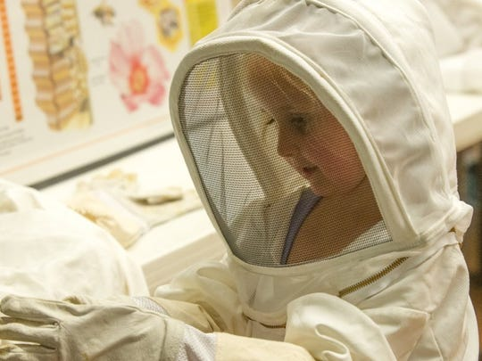 Five year-old Grace Holder of Evansville tries on a bee keeper suit at Bug Fest in the Nature Center during a past event.
