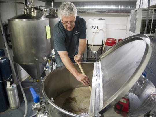 """ALEX SLITZ / COURIER & PRESS Jeff Smith, of Evansville, stirs a tank of Skinny Blonde, a golden ale style beer, at the Evansville Brewhouse in Evansville, soon after they opened. Smith has been brewing beer since 2009. """"Theres a lot of D.I.Y. in this brewery,"""" he said."""