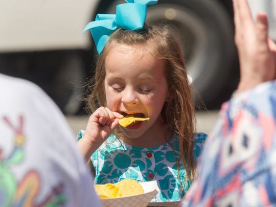 DANIEL R. PATMORE / SPECIAL TO THE GLEANER Five year-old Layla Southward of Henderson, Ky. enjoys her nachos at the Tri-Fest in Henderson, Ky., Saturday afternoon, April 16, 2016.