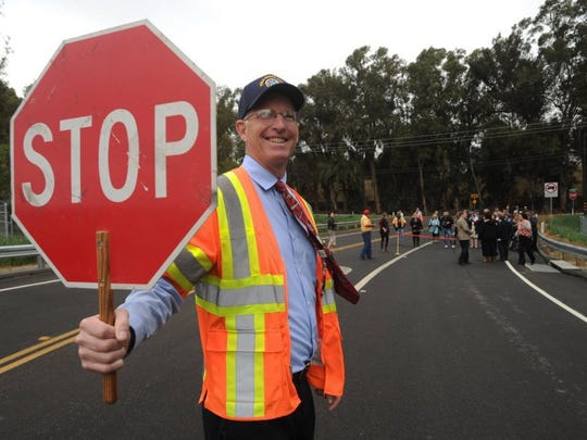STAR FILE PHOTO Cris Hook, one of the deputy directors of the Ventura County Transportation Department, stops traffic as officials prepare to cut the 2016 ribbon marking the completion of the Donlon Road Realignment Project in Somis.